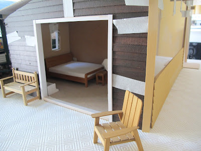 Dry fit of a dolls' house shed kit, with stained weatherboarding taped in place and white sliding door frames fitted.