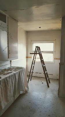 LOng view of kitchen with cracked old plaster ceiling