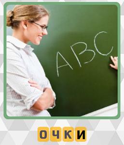 учительница в очках около доски стоит