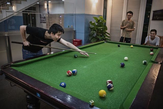 Huawei employees play pool after work at a recreation area in staff housing at the Bantian campus