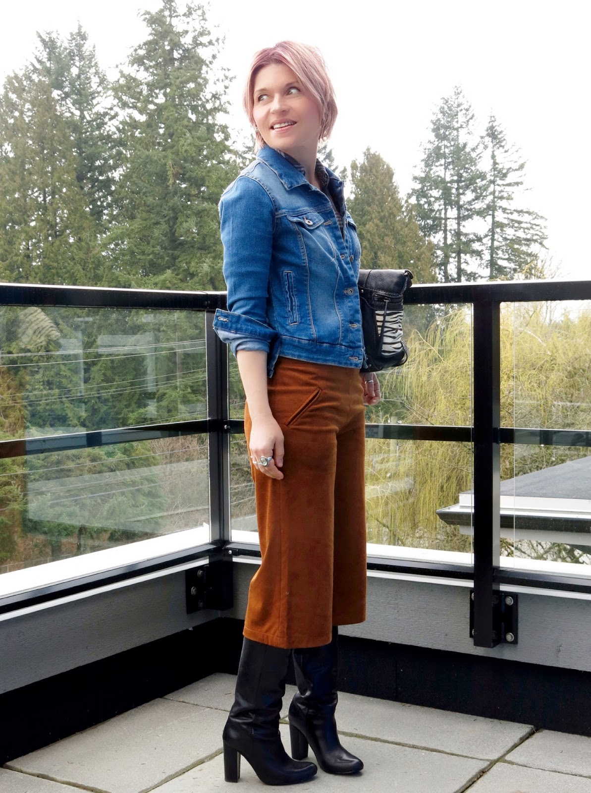 styling faux-suede culottes with a denim jacket, black knee boots, and Fossil bag