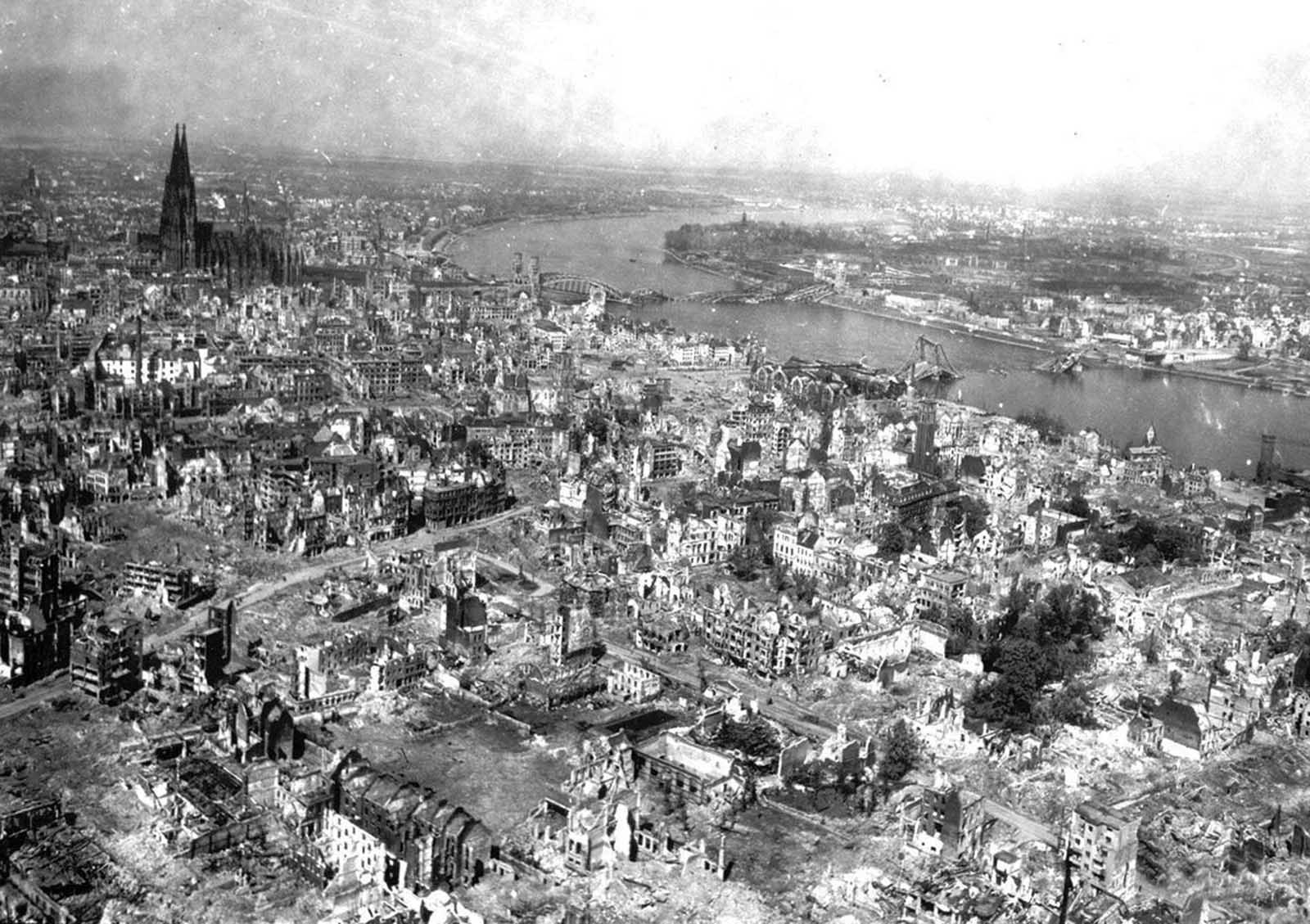 War-torn Cologne Cathedral stands out of the devastated area on the west bank of the Rhine, in Cologne, Germany, April 24, 1945. The railroad station and the Hohenzollern Bridge, at right, are completely destroyed after three years of Allied air raids.