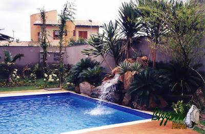 Construção de cascata de pedra na piscina com pedras ornamentais, o deck de madeira e a execução do paisagismo.