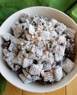 bowl of powder sugar coated dark chocolate and peppermint muddy buddies