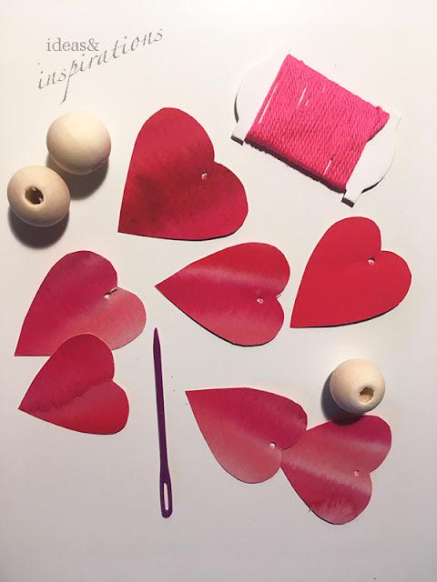 Holzperlen und rote Herzen aus Papier werden zu einer Girlande
