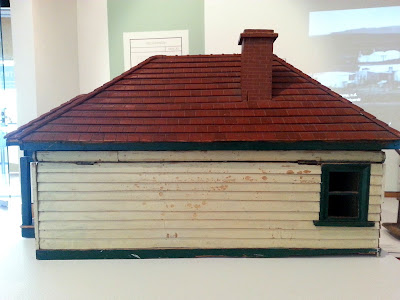 1930s vintage dolls' house bungalow on display in a museum gallery, showing the side.