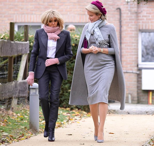 President Emmanuel Macron. First Lady Brigitte Macron is waring grey suit, and Queen Mathilde wore Merino wool cape dress