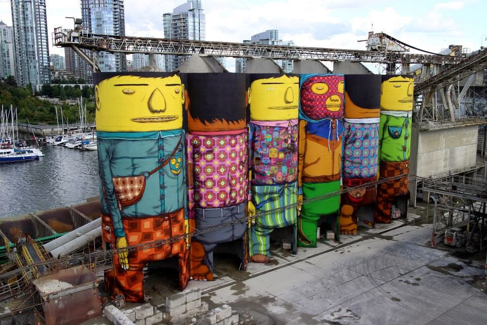 While you discovered several work in progress images a few days ago, Os Gemeos have now completed their massive piece in Vancouver, Canada for the Vancouver Biennale.