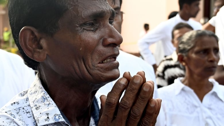 A man cries as he walks behind the coffin of a bomb blast victim after a funeral service at St Sebastian's Church in Negombo on April 23, 2019, two days after a series of bomb blasts targeting churches and luxury hotels in Sri Lanka.
