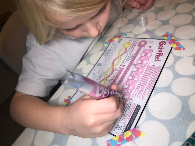 A front view of my daughter tracing out a pattern in purple