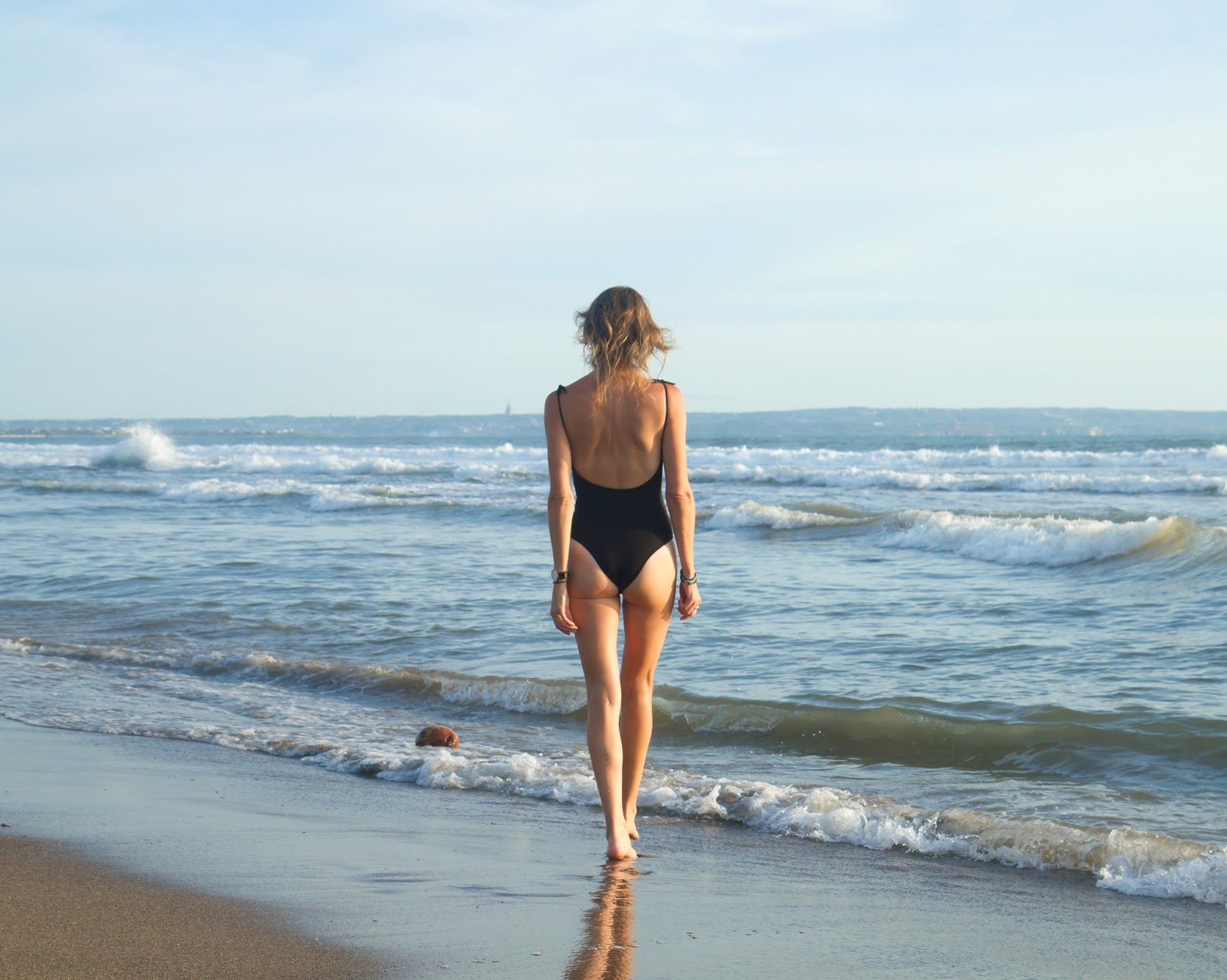 Fashion and Travel blogger, Alison Hutchinson, wearing a one-piece swimsuit at sunset