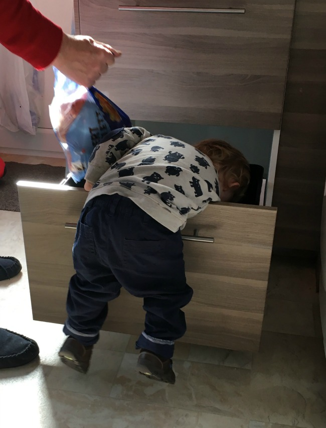 toddler leaning over drawer front. Feet off floor and head in drawer