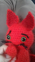 Picture shows a little red baby dragon with green eyes, close up of the face, the face expression is sorrowful, concerned, but looking very cute.