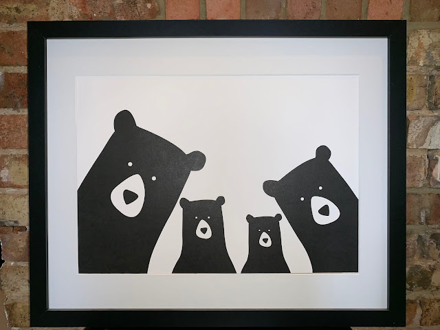 A print with black and white bold print cartoon bears looking out of the frame