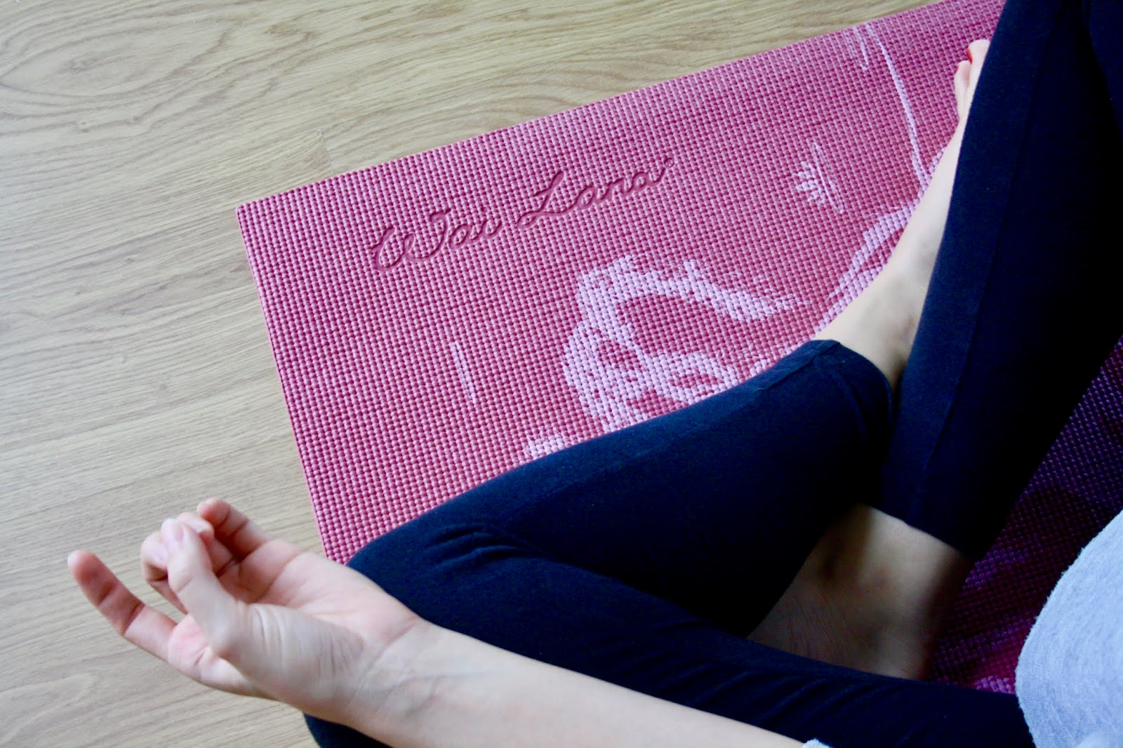 close up of abbey's crossed legs on a yoga mat, her hands in the mudra position