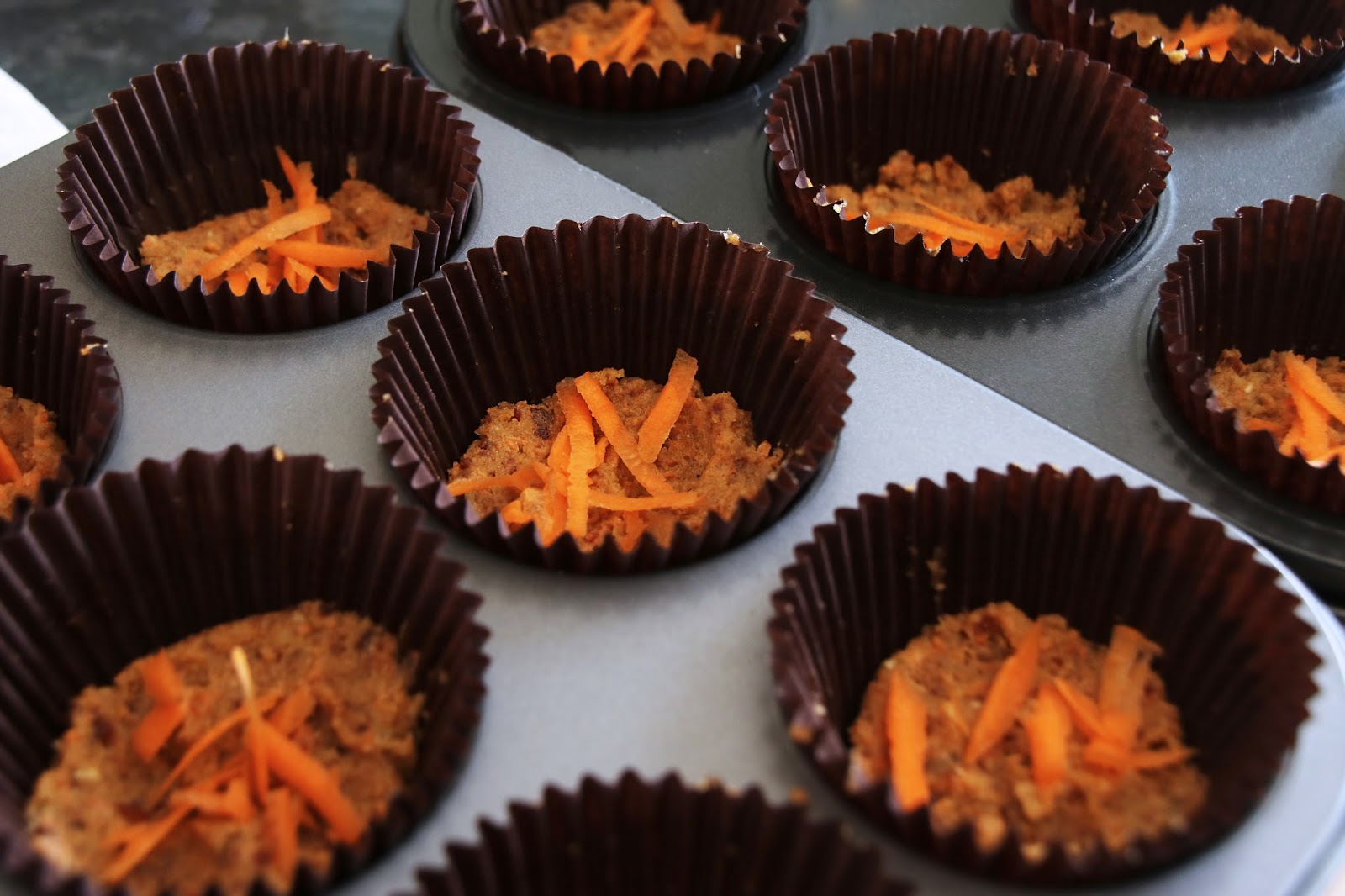 Step 3 Firmly Press Around An Inch Of The Mixture Into Each Muffin Case Top With Grated Carrot Optional And Pop It Into The Freezer Whilst You Make The