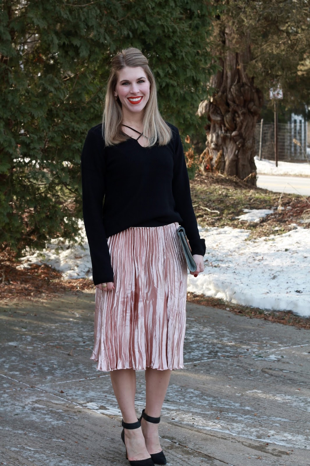 black criss cross neck sweater, pink pleated velvet skirt, black heels with strap, grey envelope clutch, valentine's day date night outfit