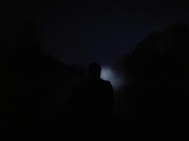 Yökuva melojan hahmo piirtyy sumuun osuvan otsalampun valossa pään ja olkapään siluetti