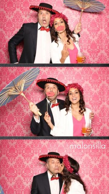 Photocall divertido de boda con una pareja posando, ella con corona de flores preservadas y labios rojos