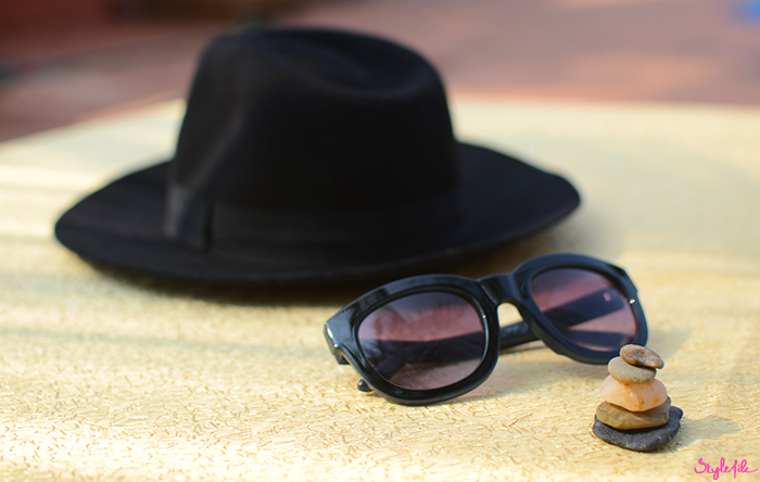 An image of a wide brimmed hat, pebbled and thick frame sunglasses at the beachside on a summer holiday break in Goa, India
