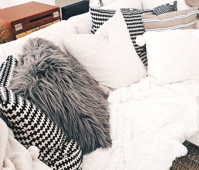 comfy couch with furry blanket and pillows