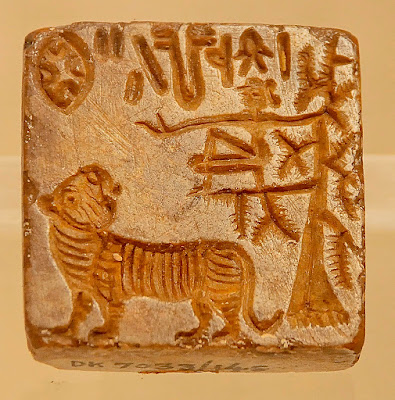 Dholavira seal showing a tiger looking back at a person seated on the branch of a tree