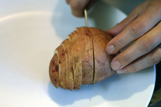 A Potato in the midst of being sliced with a knife.