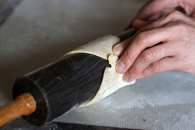 The ends of a flattened dough wrapped around a rolling pin but only slightly overlapping.