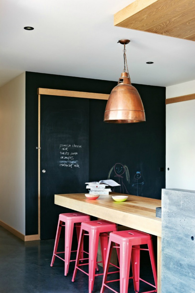 Coastal modern kitchen with painted accent wall in black chalkboard paint and hot pink barstools