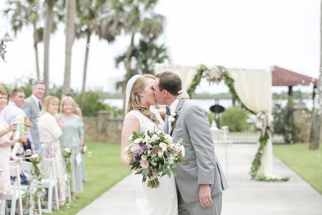 bride and groom kiss on aisle
