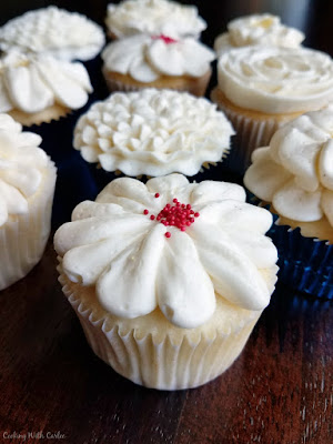 white cupcakes topped with Italian meringue buttercream flower decorations