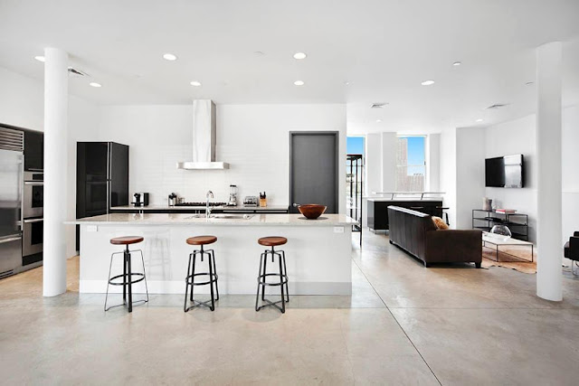 Modern kitchen in a NYC Penthouse with tile floor, stainless appliances and metal barstools