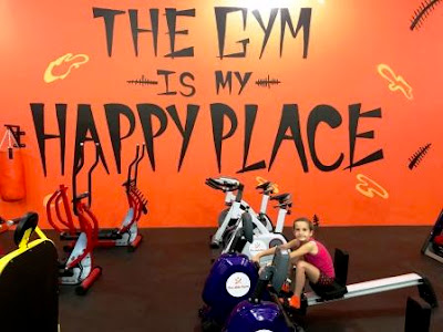 Girl sitting on kid's rowing machine at The Kids Gym with words on wal: The Kids Gym is my happy place