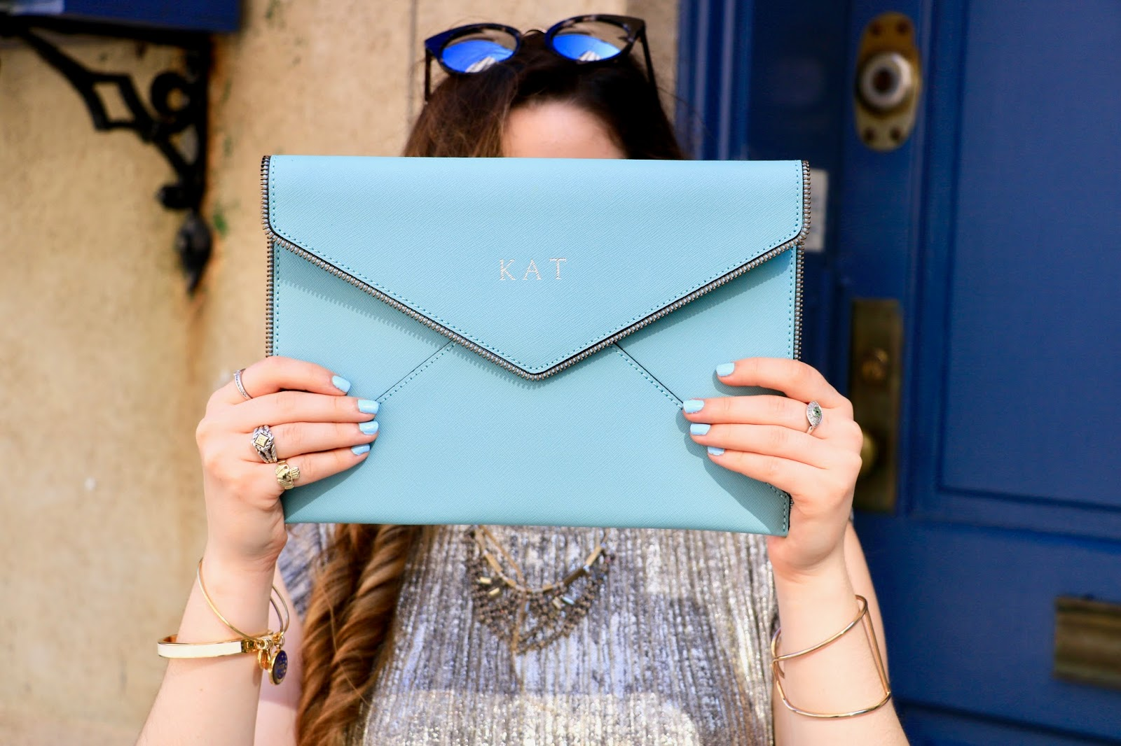 Fashion blogger Kathleen Harper holding up light blue Rebecca Minkoff clutch