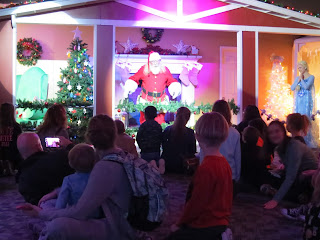 Santa Claus and Else entertain a crowd of children and parents at the Omaha Children's Museum Santa's Magic exhibit