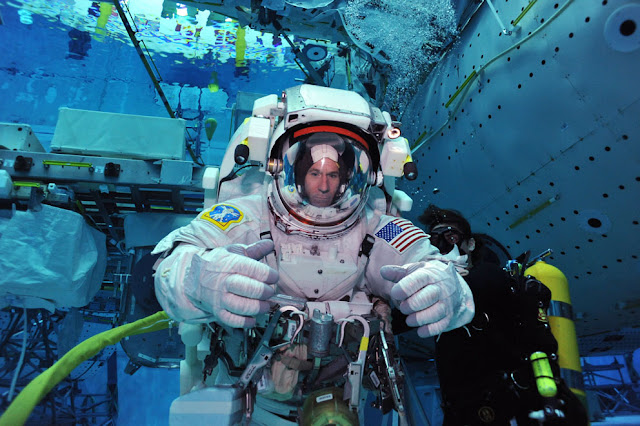 A man in a space suit in a training pool