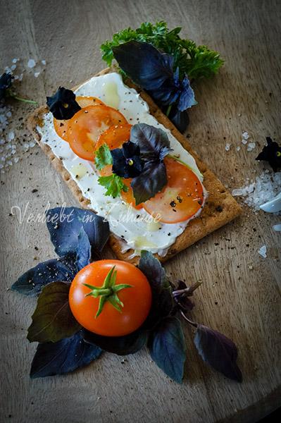 Belegtes Dinkel-Knäckebrot mit Frischkäse,Tomaten, Olivenöl, dunklem Basilikum und Stiefmütterchen