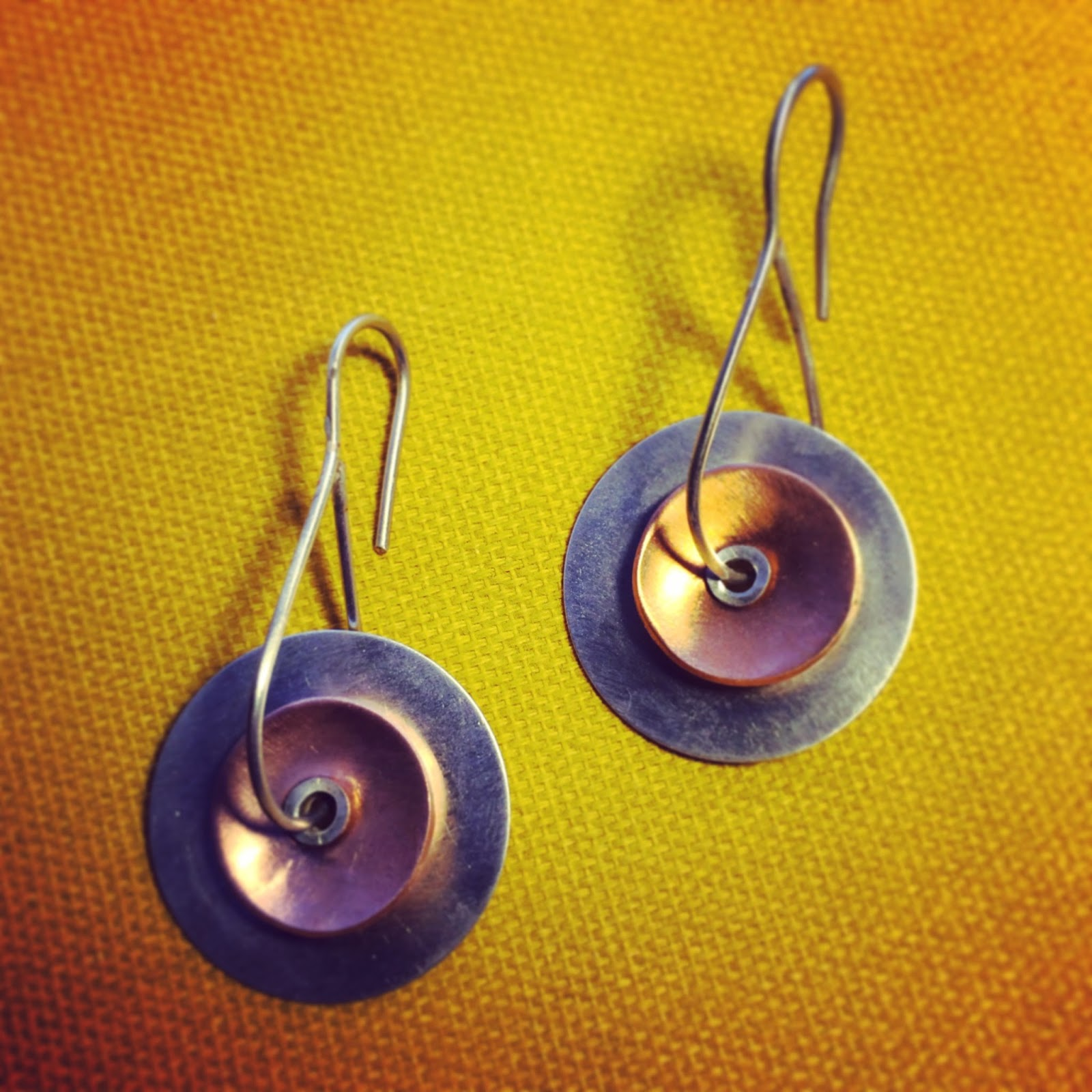 Two disc earrings made from copper and silver using a tube rivet to connect and thread the earwires through.