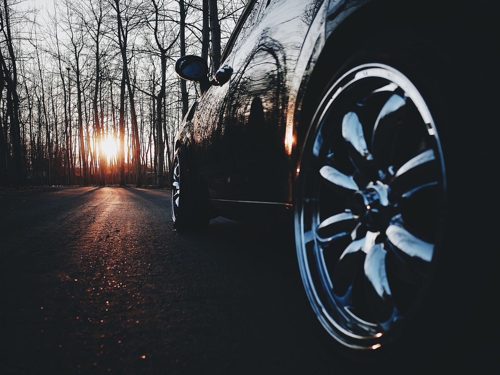 A black car parked up surrounded by trees and a sunset
