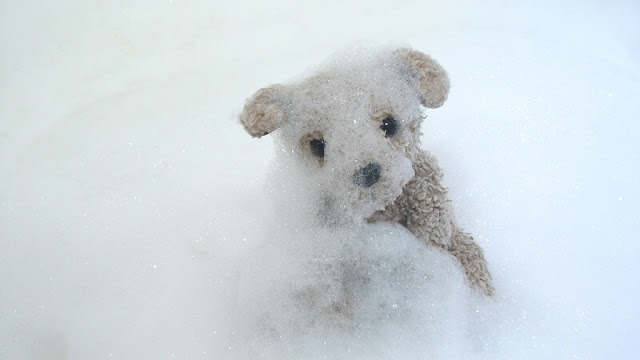Boneka beruang lucu berwarna cokelat di antara busa sabun