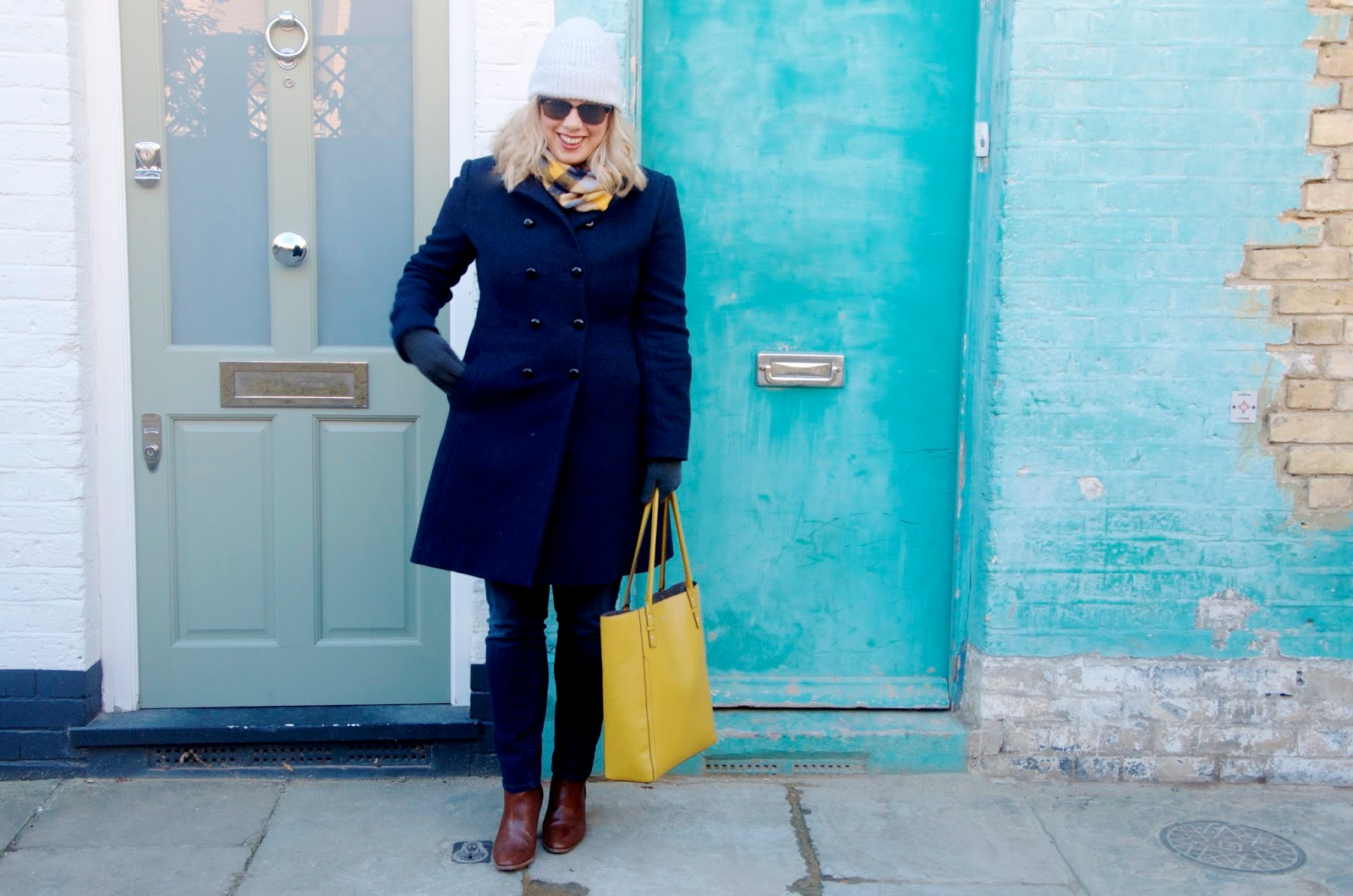 grey knit hat, navy coat, yellow bag, plaid scarf, jeans, yellow bag and grey gloves