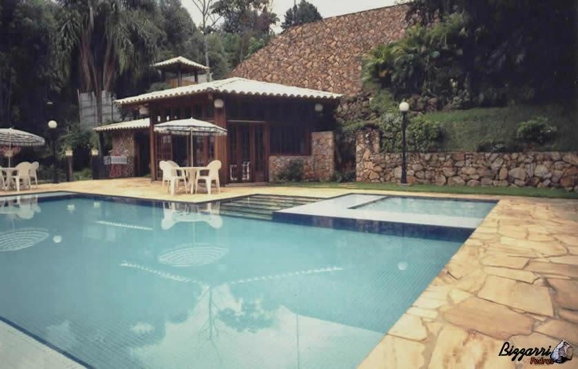 Na construção da piscina nesse terreno muito inclinado, para formar o platô, executamos a construção do muro de pedra e no passeio da piscina o piso com cacão de São Tomé.
