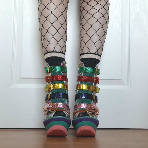feet facing forwards wearing metallic, multi coloured strap platform boots with sparkly socks and whale net tights