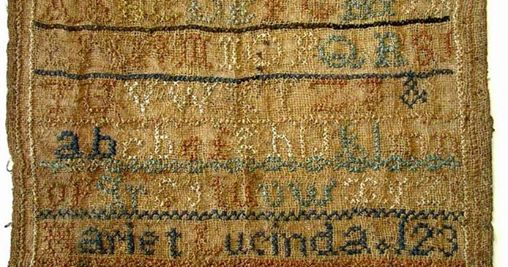 old sampler with cross-stitched alphabet, numbers and name Hariet Lucinda