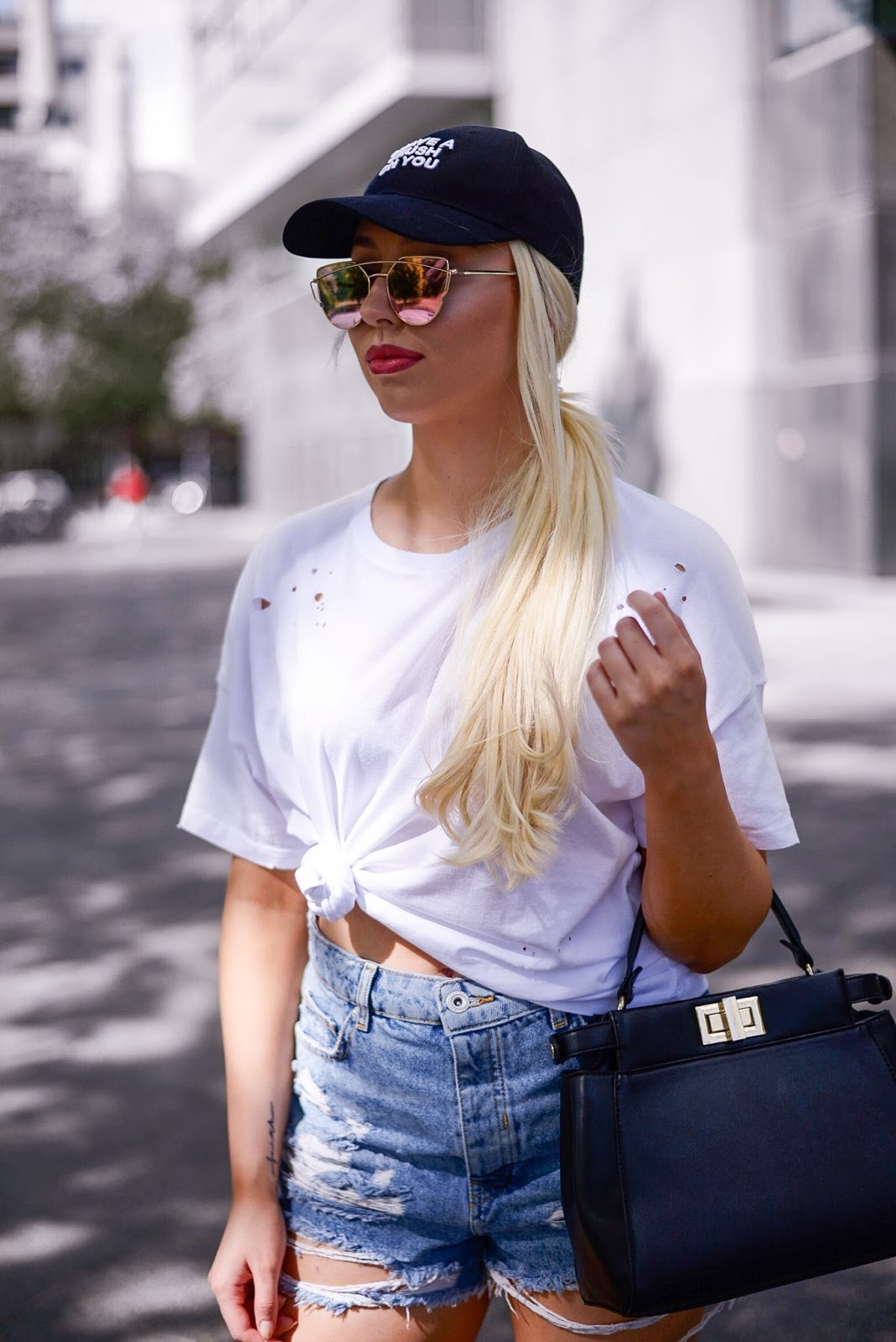 high waisted ripped denim shorts_black cap_fendi peekaboo bag