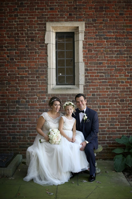 bride and groom with flower girl in front of brick wall des moines