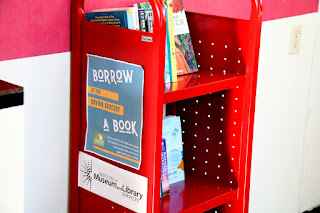 Books sit on a small red book cart. On the side it says borrow a book.