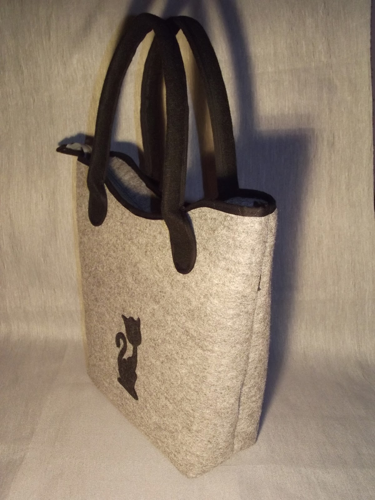6292ac96625e2 Torba z kotem na ramię uszyta jest z szarego impregnowanego filcu z  czarnymi uszami i szerokim