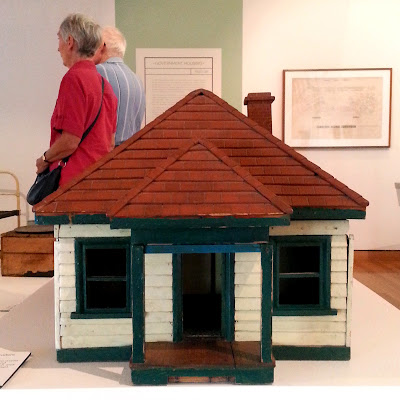 1930s vintage dolls' house bungalow on display in a museum gallery.