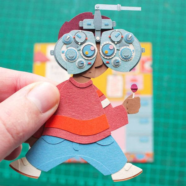 miniature paper cut boy having his eyes examined
